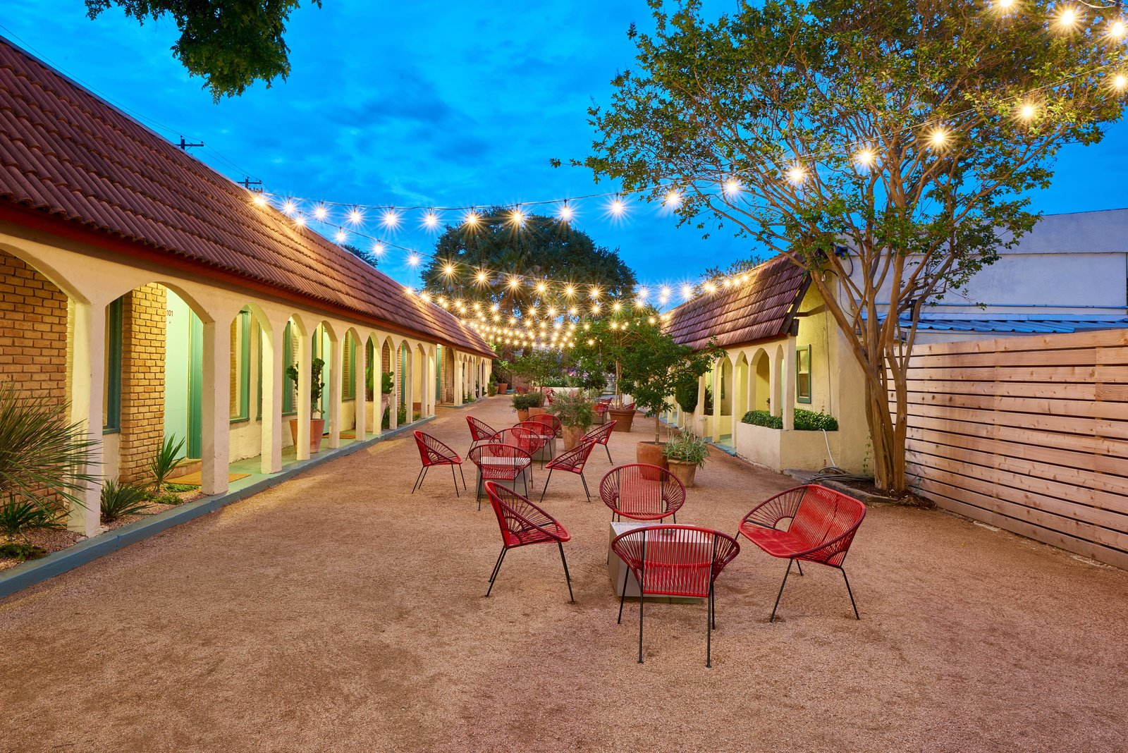 Tagged: Outdoor, Side Yard, Horizontal Fences, Wall, Large Patio, Porch, Deck, Trees, Wood Fences, Wall, and Hanging Lighting.  Photo 7 of 13 in The Rejuvenated Austin Motel Welcomes Guests With Upbeat, Midcentury-Modern Vibes