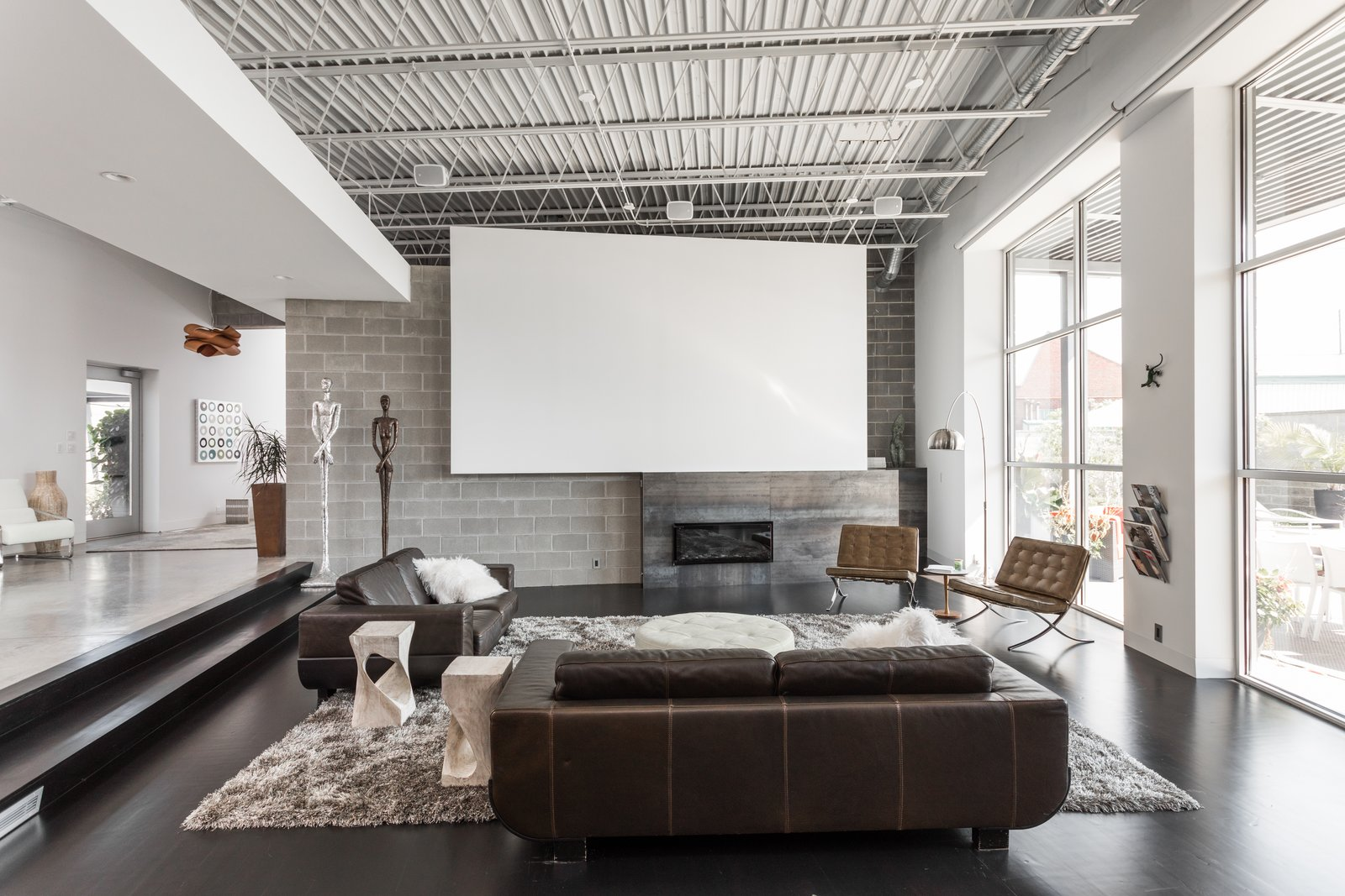 Tagged: Living Room, Dark Hardwood Floor, Chair, Sofa, End Tables, and Gas Burning Fireplace.  Photo 8 of 12 in A Converted Ink Factory in Downtown Indianapolis Asks $2.6M
