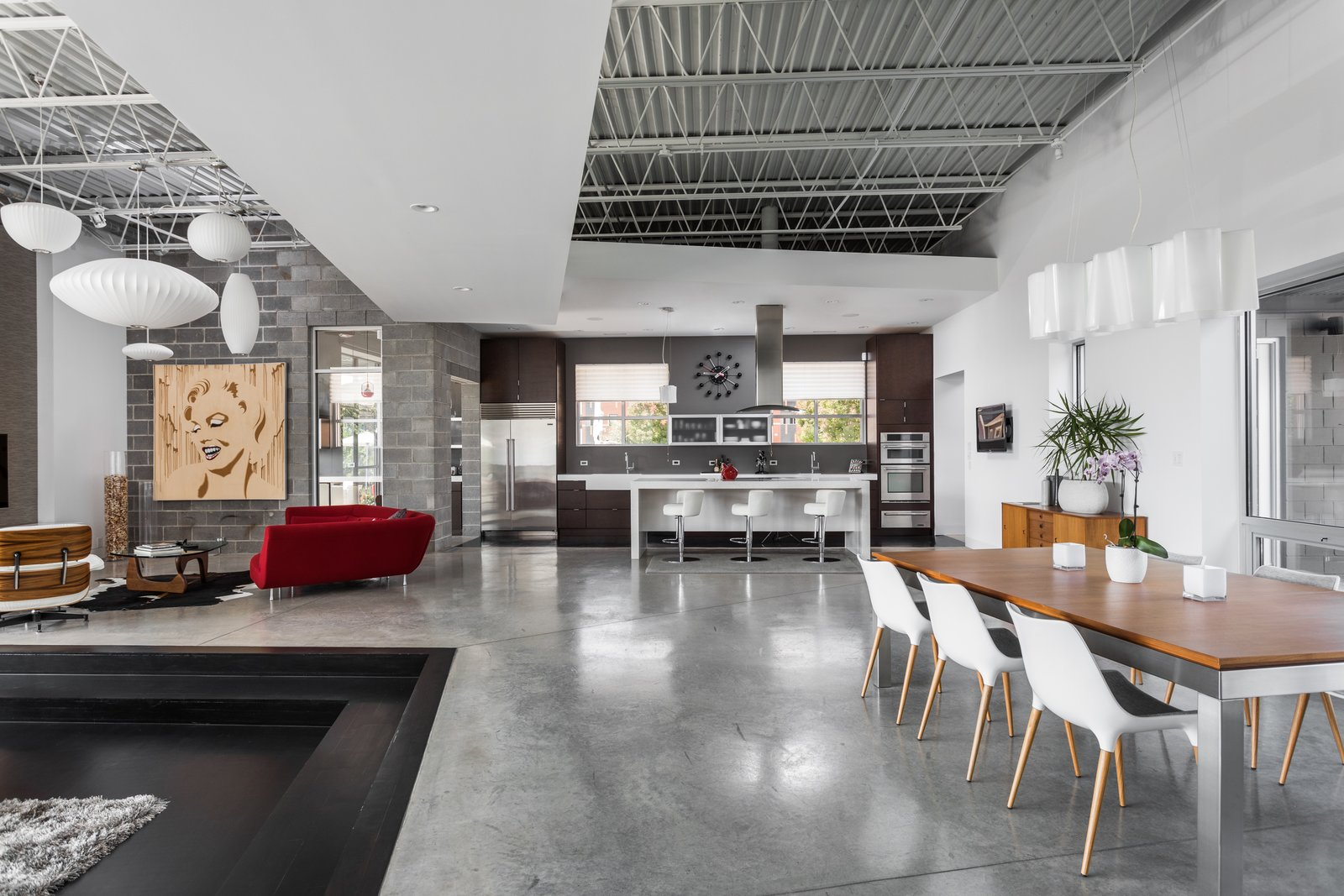 Tagged: Living Room, Chair, Sofa, Concrete Floor, Table, and Accent Lighting.  Photo 6 of 12 in A Converted Ink Factory in Downtown Indianapolis Asks $2.6M