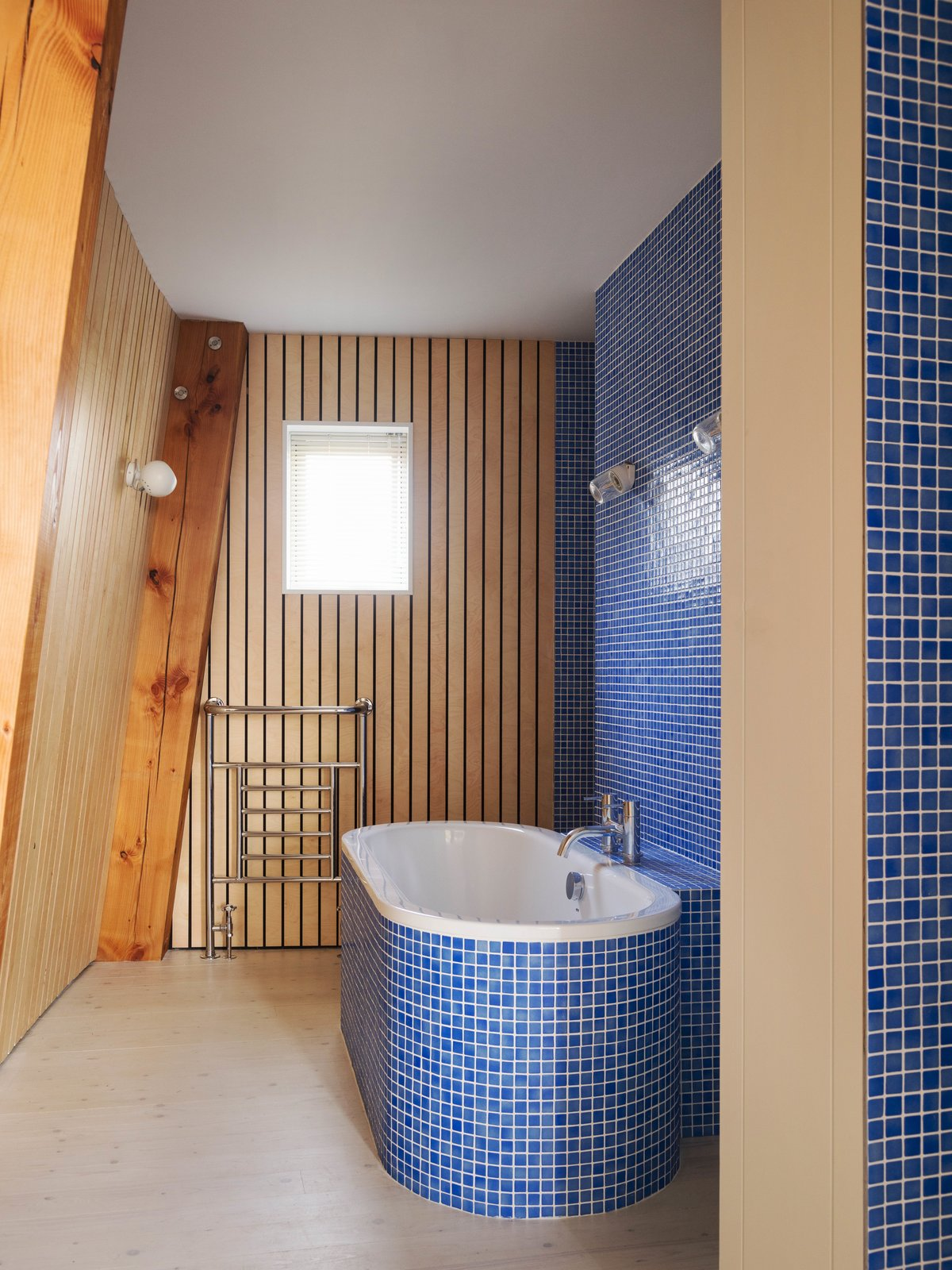 Tagged: Bath Room, Light Hardwood Floor, Soaking Tub, Wall Lighting, Freestanding Tub, and Ceramic Tile Wall.  Photo 6 of 14 in Resembling the Inverted Hull of a Ship, an English Guest House Pays Homage to the Harbor