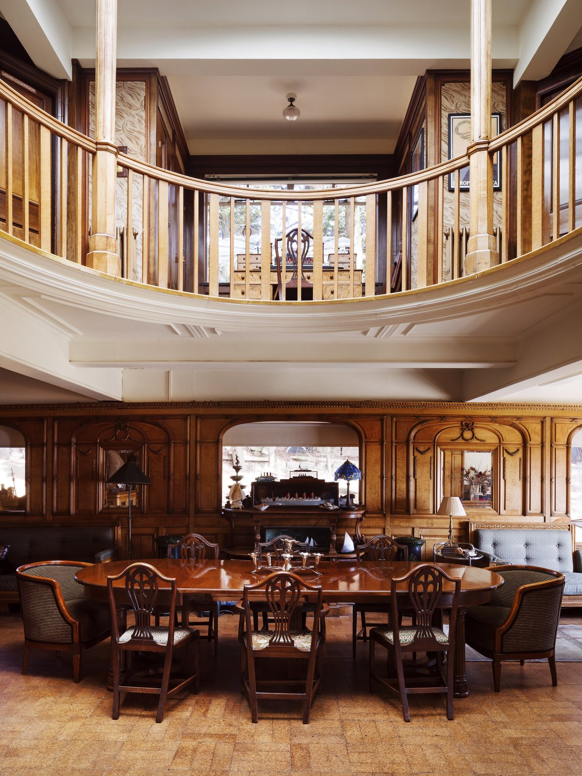 A circular gallery occupies the floor above the repurposed second-class lounge. Tagged: Living Room, Table, Chair, and Brick Floor.  Photo 4 of 14 in Resembling the Inverted Hull of a Ship, an English Guest House Pays Homage to the Harbor