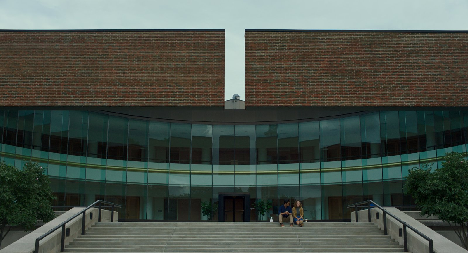 "Jin and Casey chat in front of the Columbus City Hall, designed by Edward Bassett in 1981.  Photo 6 of 8 in In the Indie Debut ""Columbus,"" Midcentury Architecture Stars Beside John Cho"