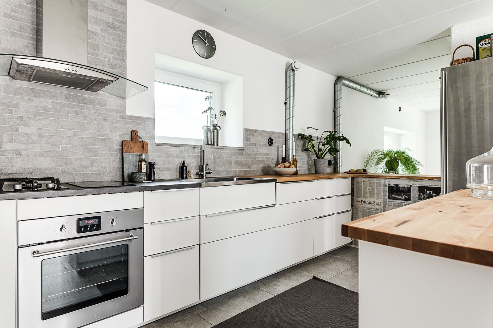 Tagged: Kitchen, White Cabinet, Wood Counter, Refrigerator, Stone Tile Backsplashe, Range, and Drop In Sink.  Photo 5 of 12 in Make This Enchanting Swedish Greenhouse Your Home For $864K