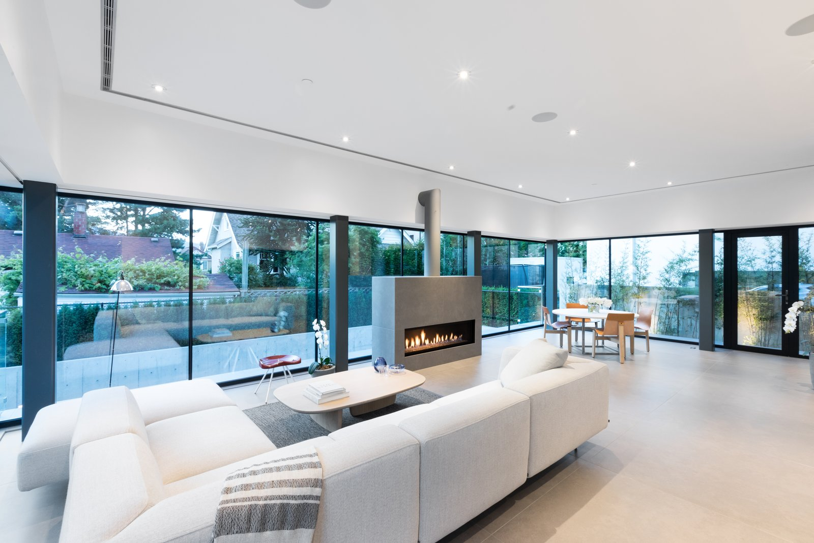 Tagged: Living Room, Ribbon Fireplace, Gas Burning Fireplace, Rug Floor, Sectional, Coffee Tables, Chair, Recessed Lighting, Floor Lighting, Table, and Stools.  Photo 4 of 12 in Wrapped in Galvanized Steel, 'Cube House' in Vancouver Asks $12.8M