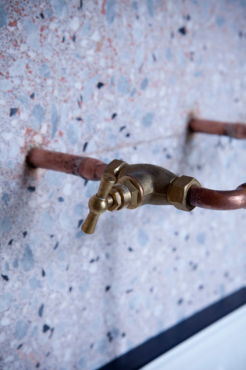 Copper piping extends out from the wall to become the faucets in the terrazzo-covered bathroom. #ChezMarieSixtine #Paris #France #designmilk Photo by Julie Ansiau  Photo 9 of 13 in 11 Examples of How to Incorporate Traditional Building Materials Into Your Modern Home from A Modern Parisian Flat Atop a Department Store