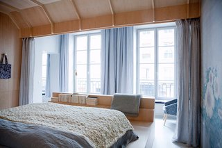 Old-World Charm Meets Modern Finishes in These 6 Parisian Apartments - Photo 6 of 12 - The bed is encased in a birchwood cocoon that looks out to grand French doors that open up to the city beyond. One wall is covered with a floral textile that brings out the calming shades of blue and gray in the space, and the bed area can be partitioned off with floor-to-ceiling curtains.