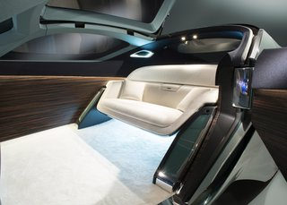 The Rolls-Royce 103EX Envisions the Brand's Next 100 Years - Photo 8 of 9 - Interior details include an expansive OLED touch-screen, Macassar wood paneling, deep-pile ivory wool carpet, and a silky wool sofa. A luggage compartment is hidden near the front wheels.
