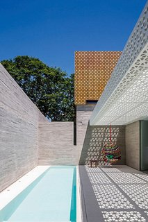 """5 Striking Designs That Use Perforated Cement Breeze-Blocks in Interesting Ways - Photo 5 of 10 - Located in São Paulo, Brazil, this outdoor space designed by Figueroa Arq employs both poured-in-place concrete and perforated concrete blocks to produce a strong contrast between the white-and-orange lattice of the blocks and the solid walls of the gray concrete. <span style=""""color: rgb(204, 204, 204); font-size: 13px;"""">Photo by Leonardo Finotti</span>"""