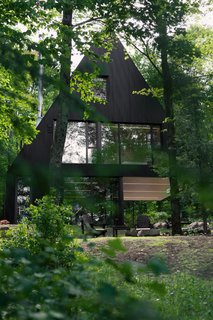 15 Modern Homes with Black Exteriors - Photo 9 of 15 - Jean Verville architecte designed FAHOUSE, a residence burrowed in the middle of a hemlock forest in Eastern Townships, Canada. The design takes inspiration from the archetypal figure of a house and doubles it with two triangular prism forms that are connected – almost like two trees growing towards the sky.