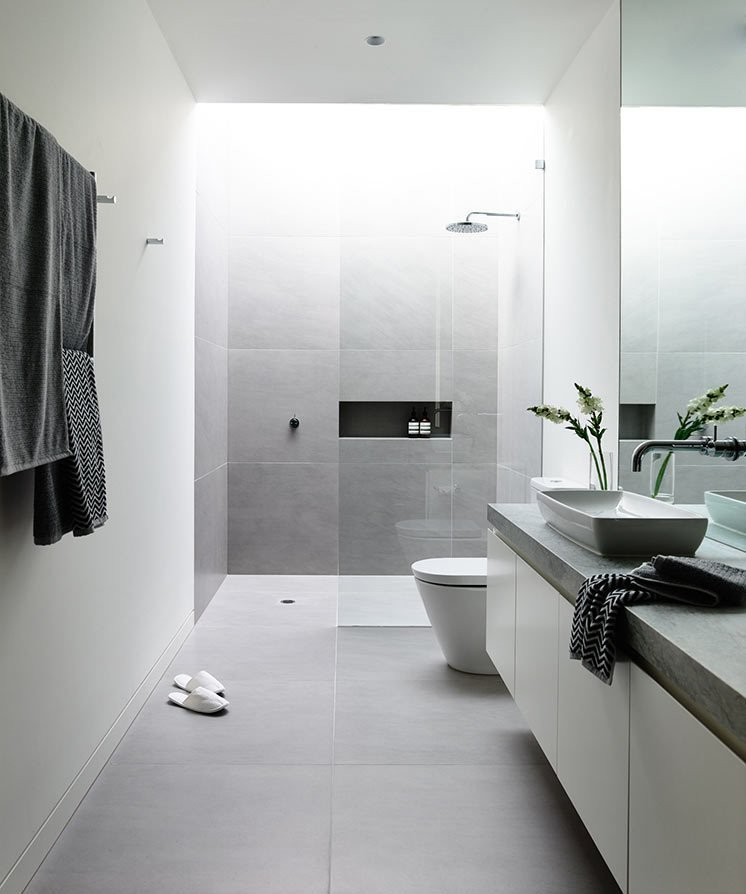 Melbourne is the location of the Canny-designed Lubelso Hawthorn Concept Home where one of the bathrooms has large, soft grey tiles on the floor that continue up the sides of the shower walls. A skylight above the shower keeps the space full of light.  Photo by Derek Swalwell  renovation by Tony Youssef from 10 Minimalist Bathrooms of Our Dreams
