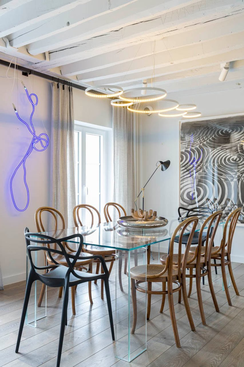 The dining room features a Glas Italia table that's paired with vintage Thonet chairs and two black Kartell chairs. The neon art is by Gun Gordillo and the piece on the right is by Alexandre Arrechea.  A Parisian Pied-À-Terre by Piret Johanson Studio #designmilk