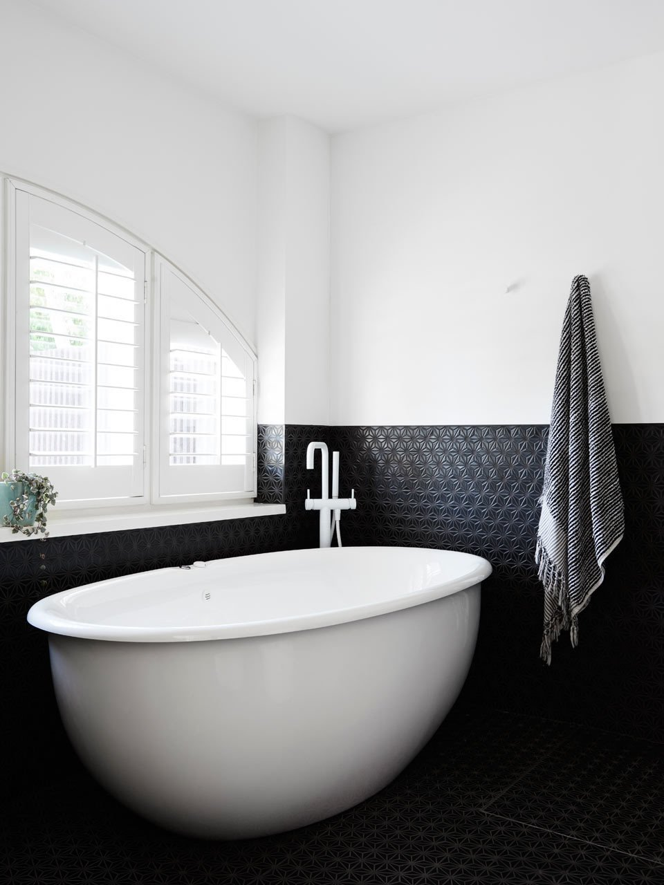 #designmilk #northbourne #architecture #melbourne #modern Photo by Eve Wilson  The new master bathroom is outfitted with charcoal Japanese mosaic tiles, which contrast the white paint and fixtures.    Tubs by Jenny Xie from A Melbourne Home is Renovated for a Growing Family