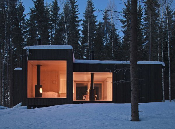 Shaped like a cross, the Four-cornered Villa offers four different views of its location on an island in Finland. Avanto Architects created a black exterior, dotted with large windows, to make it invisible from the nearby lake.  Photo 6 of 11 in 10 Modern Wintry Cabins We'd Be Happy to Hole Up In