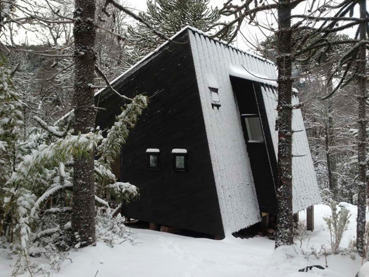 This winter retreat located in a forest in the Araucanía Region of Chile was designed by MC2 Arquitectos to face a small waterfall. One side features a large window, while the other walls has smaller windows that focus on specific views and provide ventilation for the house. Its painted brown exterior helps it blend into the surrounding landscape. 10 Modern Wintry Cabins We'd Be Happy to Hole Up In - Photo 7 of 11