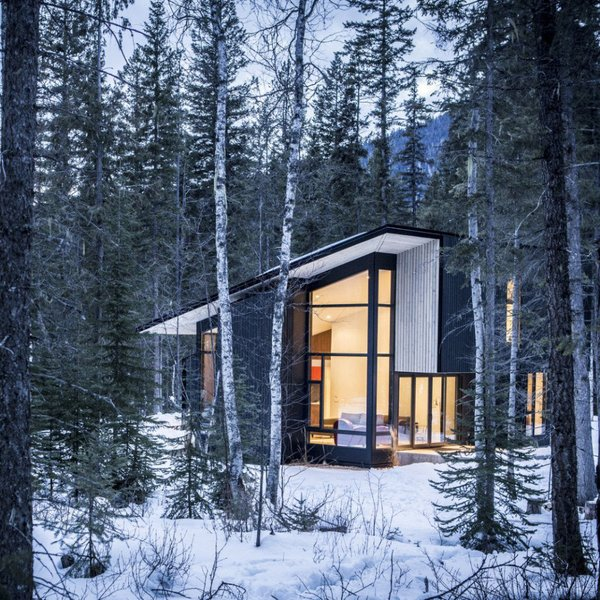 Form & Forest have designed the ultimate modern cabin that you can actually rent! Surrounded by wilderness, the retreat sits on the Blaeberry River near Golden, British Columbia with vaulted ceilings in the living room that afford incredible views of the forest, mountains, and river.  Photo 8 of 11 in 10 Modern Wintry Cabins We'd Be Happy to Hole Up In