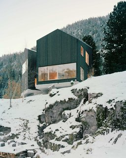 10 Modern Wintry Cabins We'd Be Happy to Hole Up In - Photo 10 of 10 - Lacroix Chessex Architectes realized La Maison aux Jeurs, a cabin in Les Jeurs, Switzerland situated on a rocky hill above the road. The structure is divided into two volumes that are angled 45 degrees apart with a connection on the mountain side. Both volumes are designed with different views of the valley below.