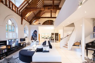 Traditional Churches Become Modern Homes - Photo 1 of 10 - A Victorian-style church in London was converted by Gianna Camilotti Interiors into a modern home while keeping its historic charm. The outside may remain a traditional red brick, but the interior features white walls and floors, along with arched windows and wooden beams.