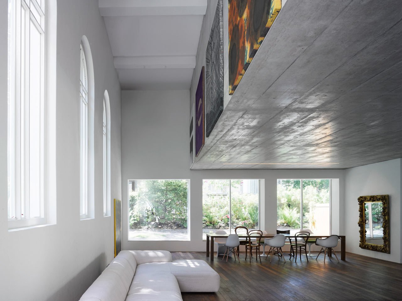 Located in Bern, Switzerland, the 1924 Luke Chapel went from rundown to two new modern homes by Morscher Architekten. To prevent covering the large church windows and to avoid adding support posts, the top apartment is suspended within a concrete box above. The box's facade was the perfect place to display artwork.  Photo 10 of 10 in Traditional Churches Become Modern Homes
