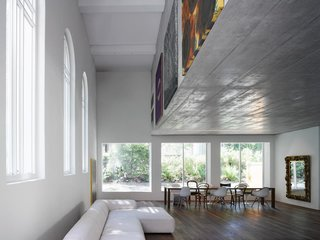 Traditional Churches Become Modern Homes - Photo 10 of 10 - Located in Bern, Switzerland, the 1924 Luke Chapel went from rundown to two new modern homes by Morscher Architekten. To prevent covering the large church windows and to avoid adding support posts, the top apartment is suspended within a concrete box above. The box's facade was the perfect place to display artwork.