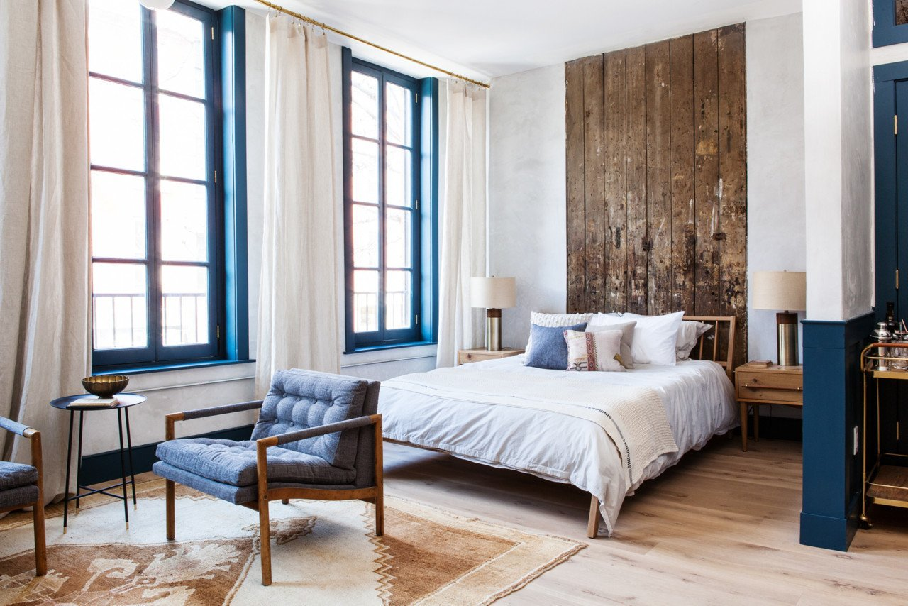 The interiors are designed by Jersey Ice Cream Company who decorated each suite with a mid-century modern meets industrial style. Accent walls, frames, and cabinetry are painted a deep cerulean blue for a calming vibe; brass fixtures and soaking claw foot tubs give a classic feel to a modern hospitality experience; and a curated collection of art and books brings the trending concept home (no pun intended). Tagged: Bedroom, Chair, Night Stands, Light Hardwood Floor, Rug Floor, Lamps, and Bed.  Photo 1 of 18 in Lokal: A Classic Hotel with a Modern Invisible Service