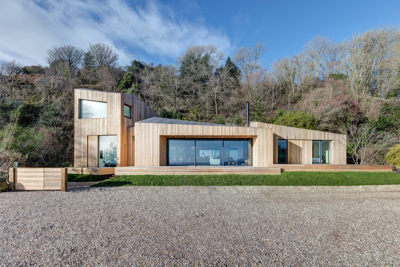The home's design began with a traditional cabin form that broke off from there to split, twist, and rotate into four pods. The residence perfectly blends with the surrounding landscape with its larch lad exterior.