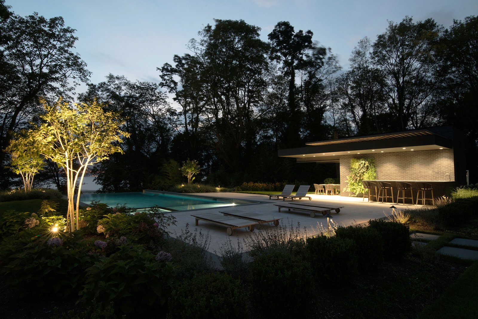 Landscape and a green wall provide an organic counterpoint to the Free Float Pool House's contemporary materials.  Free Float Pool Cabana by The UP Studio