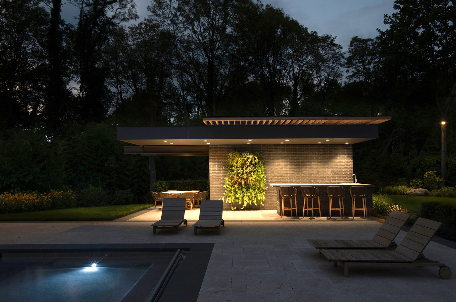Lighting at UP Studio's Free Float Pool House creates a dramatic setting for entertaining at night.