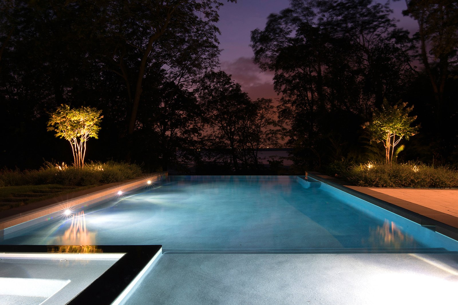 The pool, lighting, and landscape frame dramatic views of sunsets over the Long Island Sound.