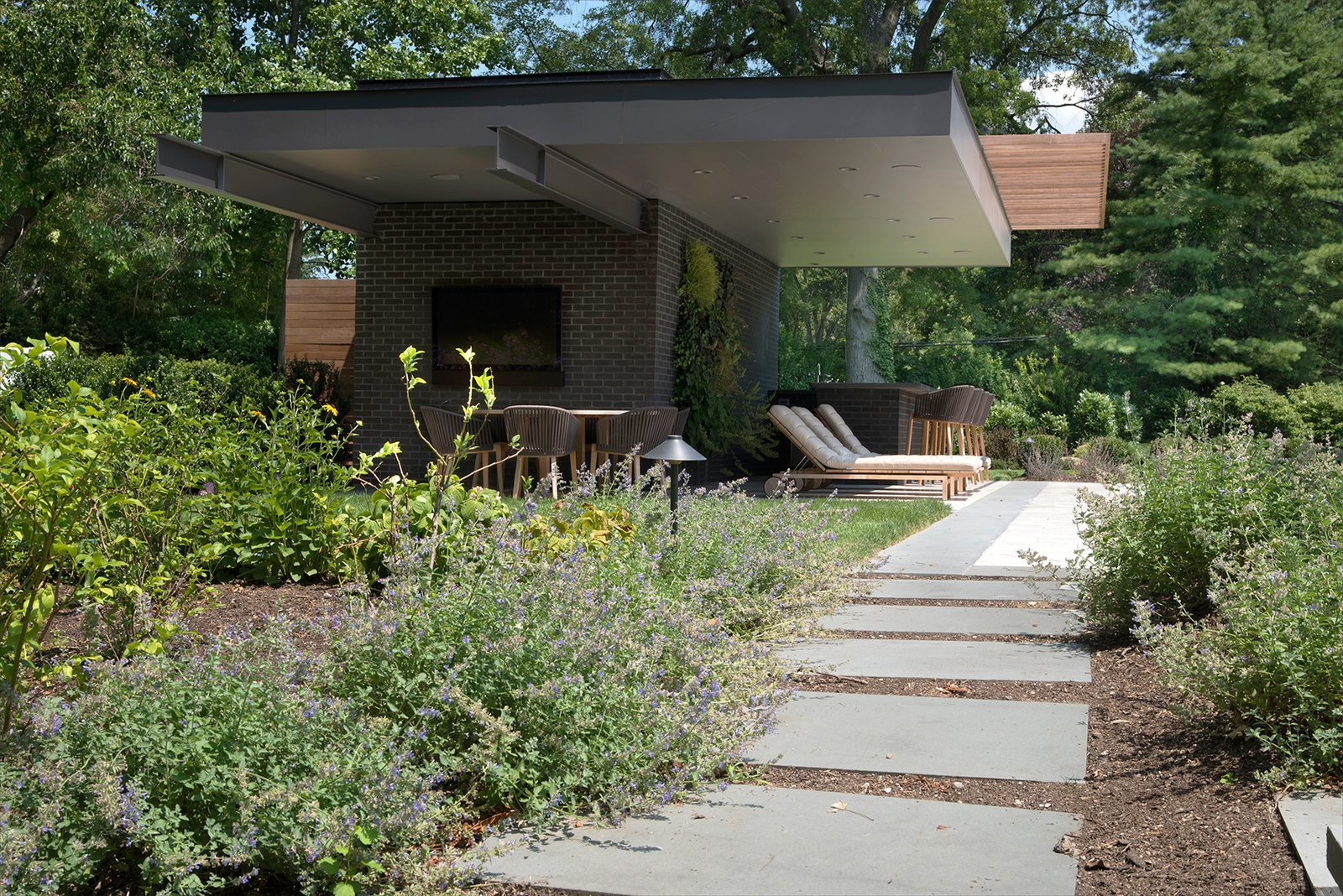 A view of the Free Float Pool House from the garden of lush plantings by Bayview Landscape Architecture.
