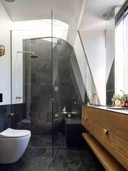 The master ensuite provides a brass shower under the stars and a toilet with a view of the clouds. The slate tiles can be used as blackboards. © Justin Alexander   Photo 19 of Bougainvillea Row House modern home
