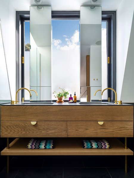Solid American oak and brass Hafele handles are used in the vanity. Slender mirrors allow plenty of light to bathe in. © Justin Alexander Photo 20 of Bougainvillea Row House modern home