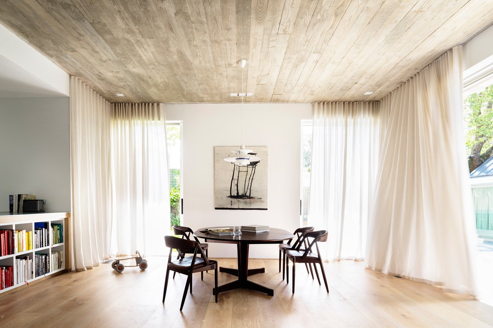 Downstairs, sheer curtains provide privacy and soften the large family room, while a concrete ceiling, traditionally framed by recycled hardwood timber contrast with a Porters oak floor. © Justin Alexander  Loggia in Arcadia by Luigi Rosselli Architects