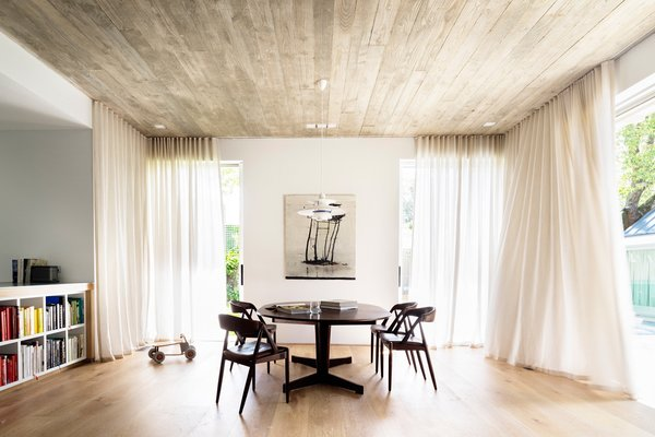 Downstairs, sheer curtains provide privacy and soften the large family room, while a concrete ceiling, traditionally framed by recycled hardwood timber contrast with a Porters oak floor. © Justin Alexander Photo 7 of Loggia in Arcadia modern home