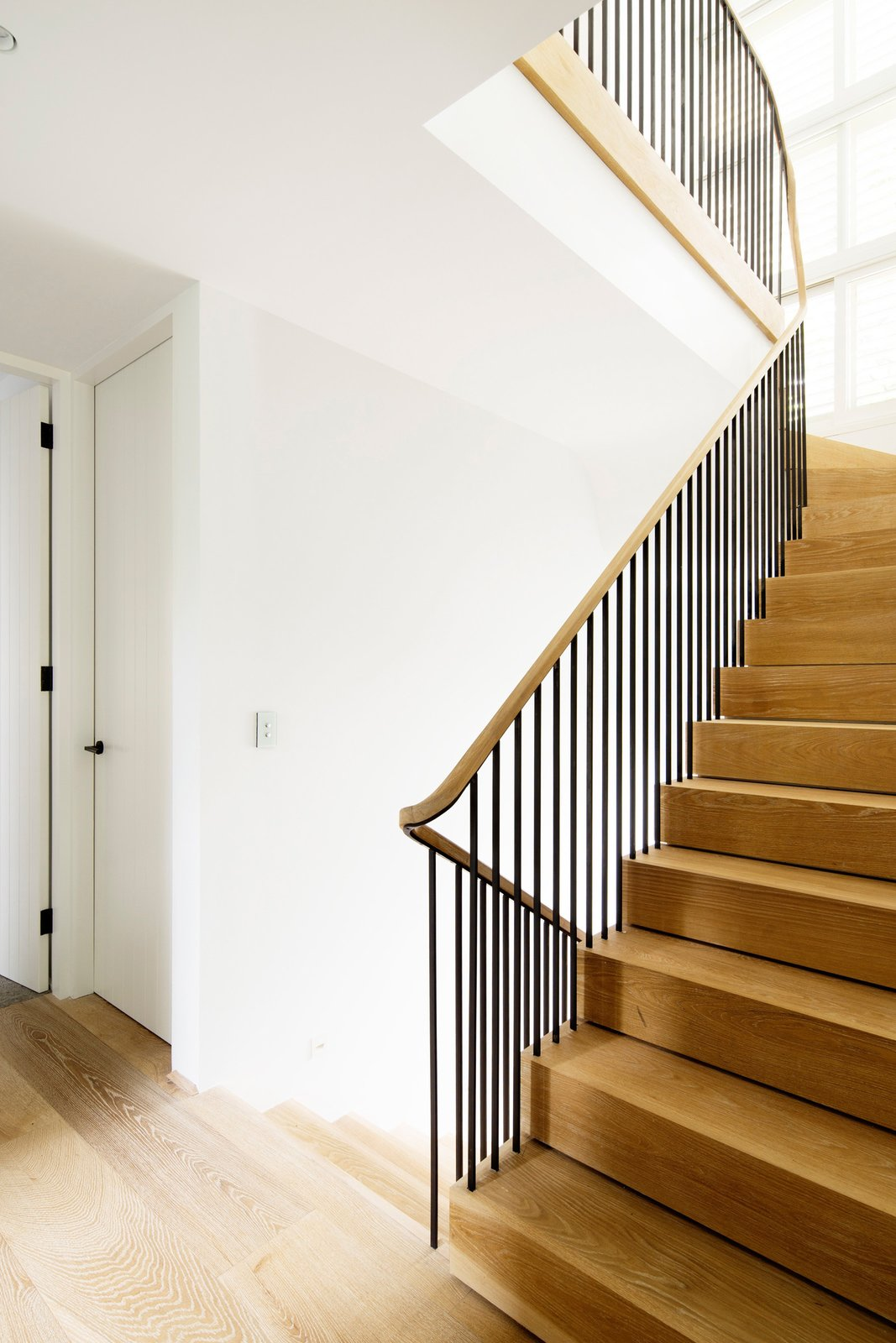 The oak stair is bathed in light from a shuttered vertical window and connects the three storeys of the residence. © Justin Alexander