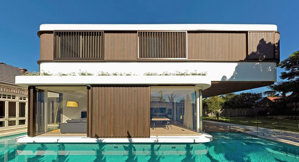 The first floor bedrooms cantilever towards the backyard, being larger than the ground floor living spaces. The two rectangular volumes are shifted, each with different wall constructions: very glazed and open downstairs, and closed upstairs. The bedrooms have two sliding shutters, manually controlled. © Justin Alexander Photo 5 of The Pool House modern home
