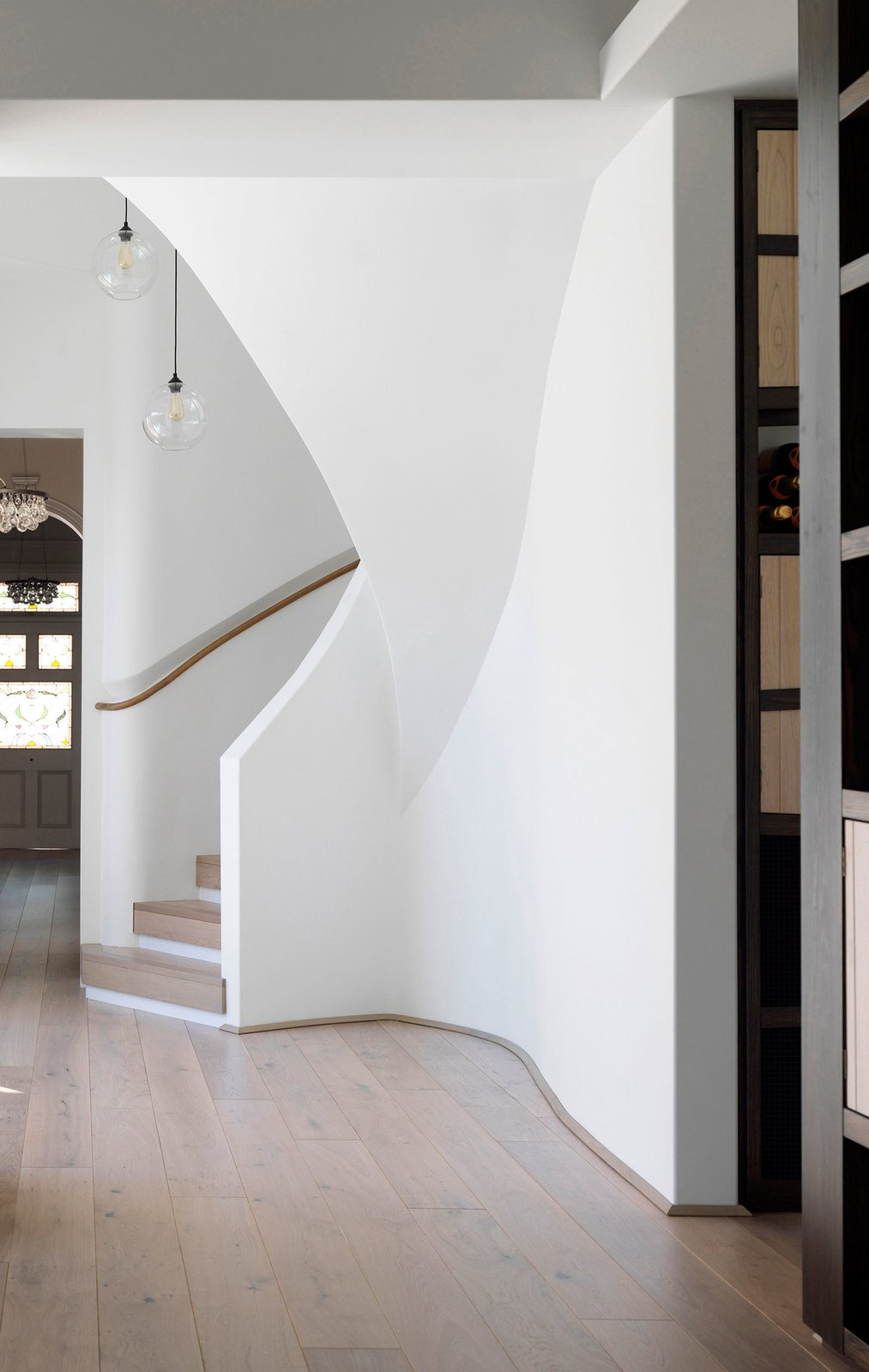 Linking the old house to the new is the spiral storage stair. The joinery to the right is a wine store. © Justin Alexander   The Pool House by Luigi Rosselli Architects