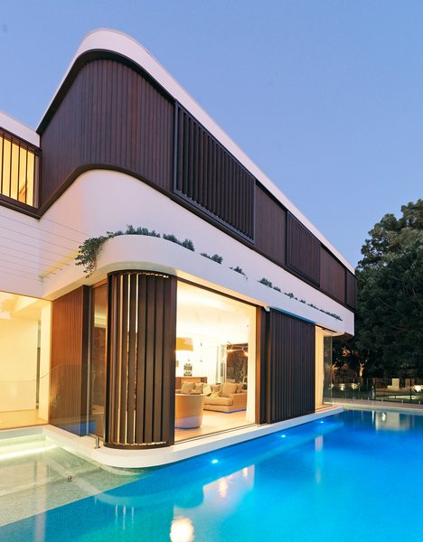 "By dividing the first floor walls in three strips, the horizontality is reinforced; a lower structural spandrel below the windows, finished with an acrylic white render, a middle window strip with timber shutters and timber ""log cabin"" weatherboards, and an upper roof edge also finished with an acrylic render. © Justin Alexander Photo 9 of The Pool House modern home"