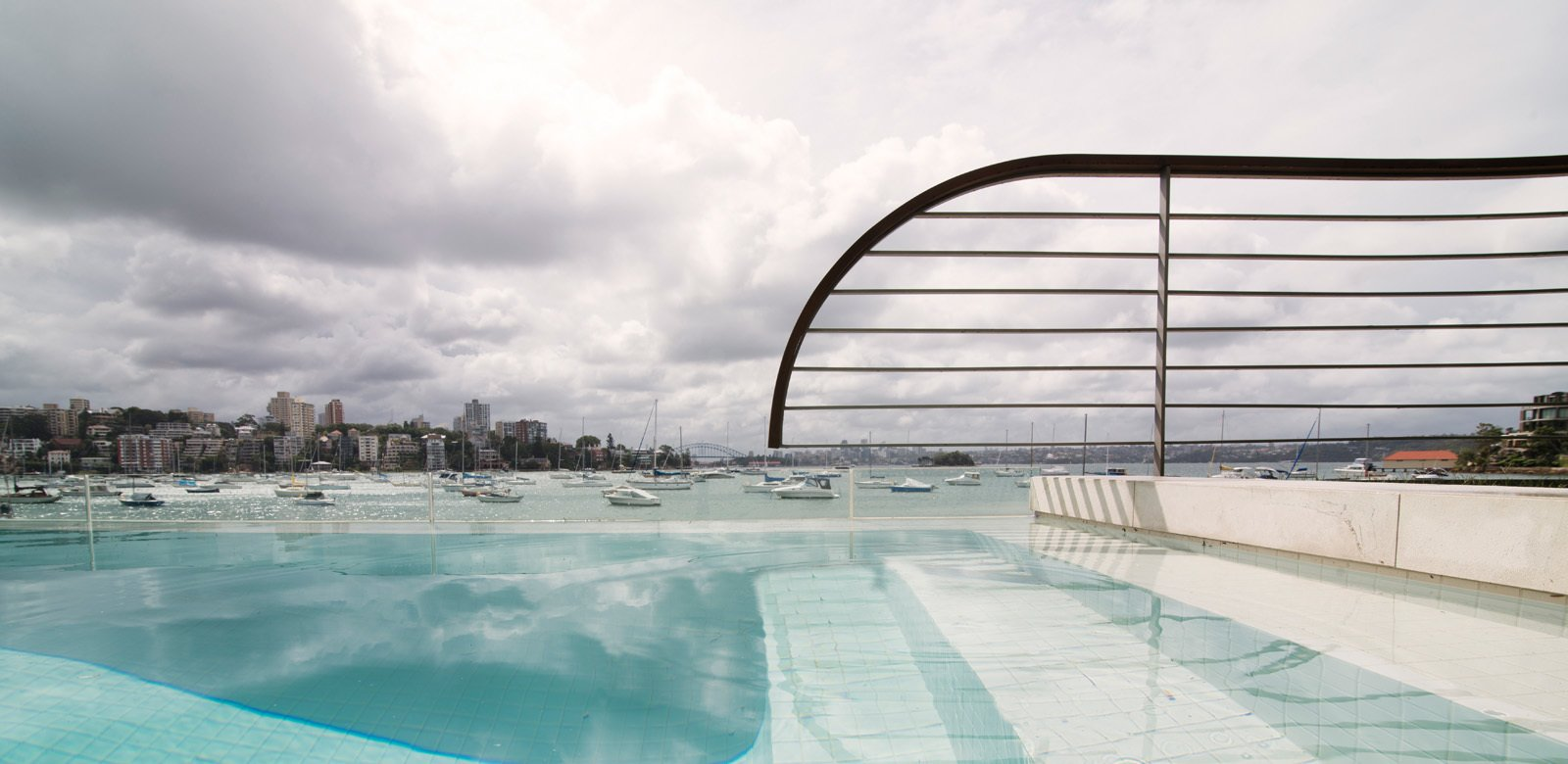 Sydney Harbour's water continues in the white tiled swimming pool, a glass splash protection screen limits any pool water overflow onto the public beach. © Edward Birch