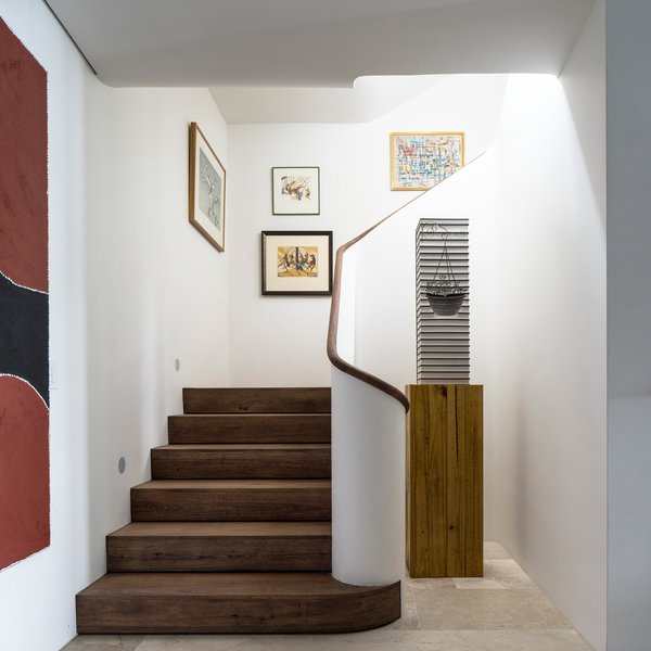 The vertical gallery of paintings terminates at the bottom of the stairs with a sculpture. © Justin Alexander Photo 13 of Harbour Front-Row Seat modern home