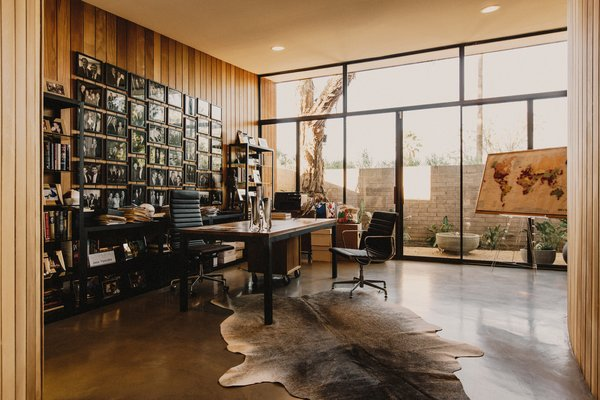 Modern home with office, study, bookcase, chair, desk, and concrete floor. Home office opens up to a courtyard with a bubbling water fountain Photo 3 of Curves House