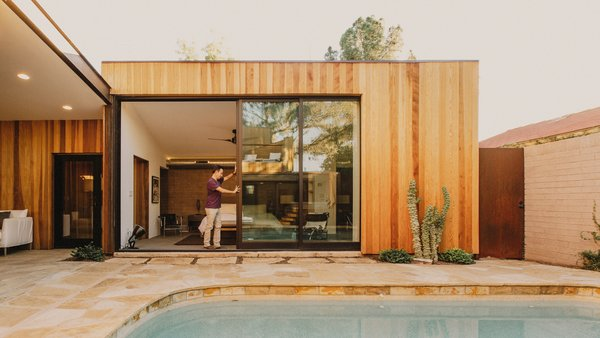 Modern home with doors, metal, sliding door type, and exterior. The doors of the master suite pocket behind the redwood to allow the space to extend to the pool courtyard Photo 10 of Curves House
