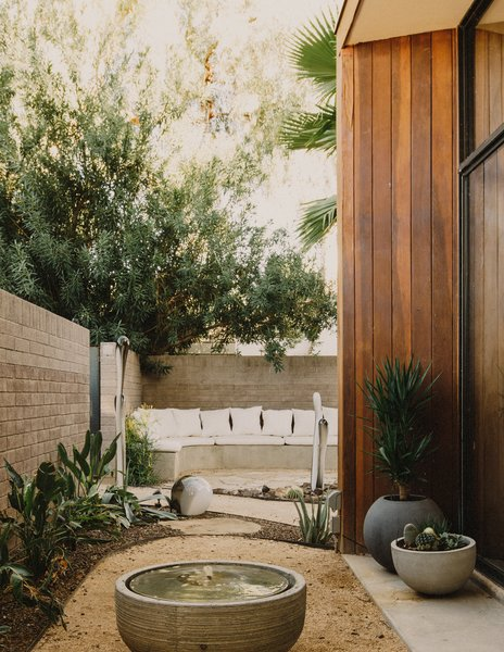Modern home with outdoor, front yard, desert, raised planters, stone patio, porch, deck, decomposed granite patio, porch, deck, and shrubs. View from the office courtyard to the entry courtyard that features a custom concrete bench Photo 15 of Curves House