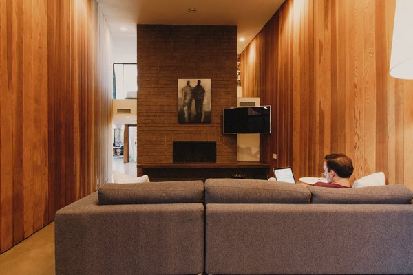Modern home with living room, sofa, ceiling lighting, concrete floor, standard layout fireplace, and wood burning fireplace. Living room clad with redwood on both sides with a concrete block fireplace in the center of the double height space Photo 8 of Curves House