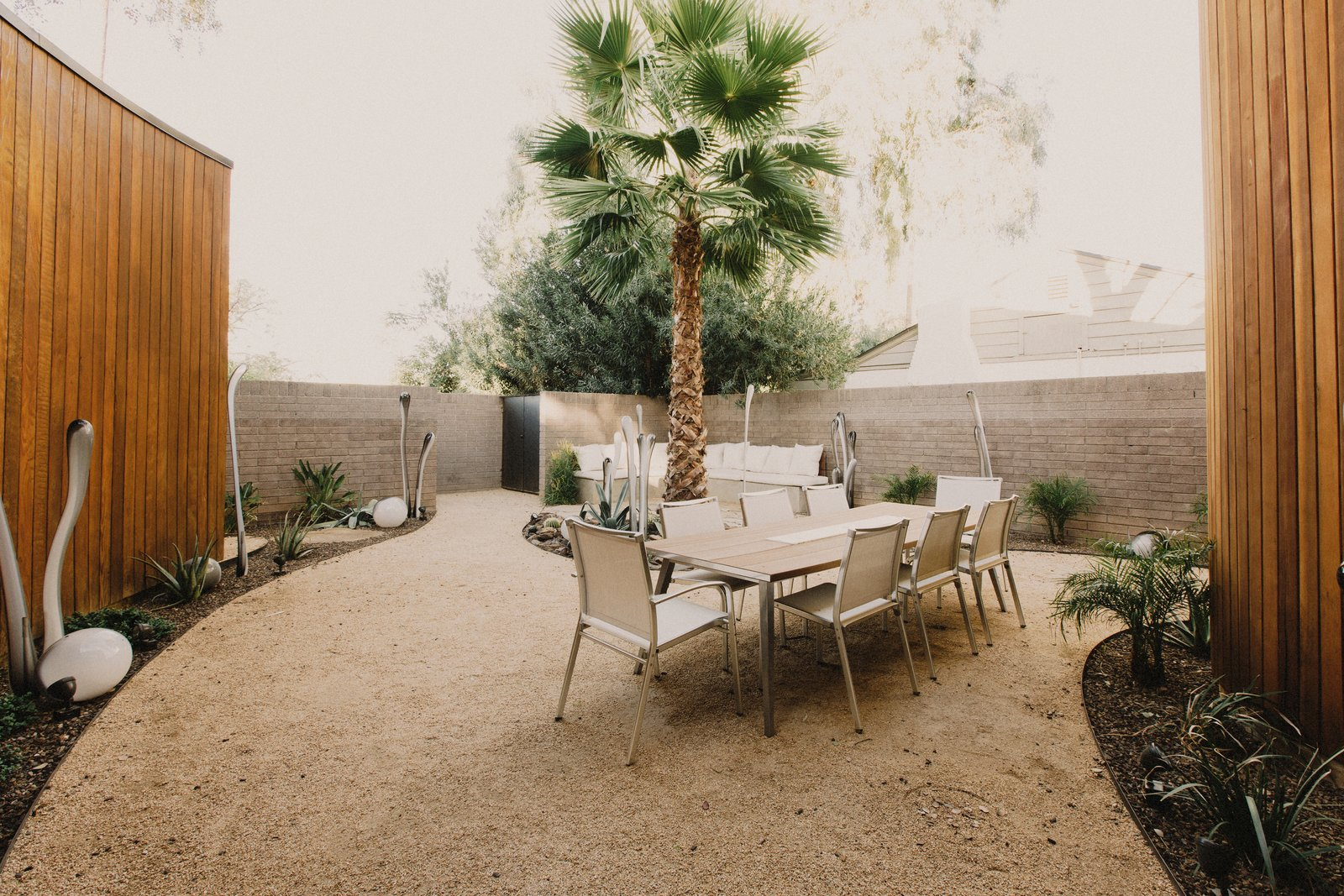 Front courtyard extends living functions outside of the house, allowing the house to live much larger than its footprint Tagged: Outdoor, Desert, Shrubs, Trees, Decomposed Granite Patio, Porch, Deck, and Stone Patio, Porch, Deck. Curves House by The Ranch Mine