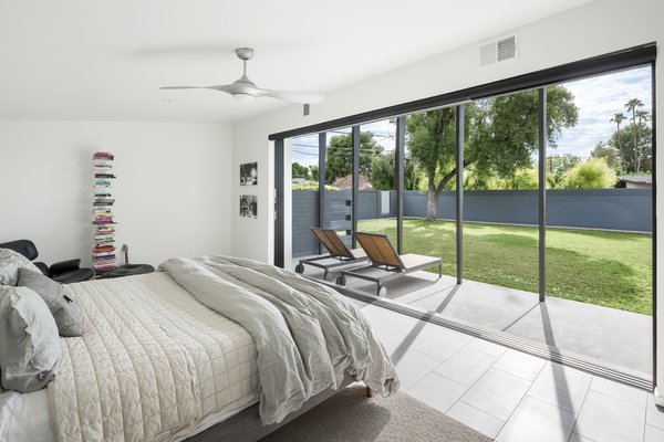 Modern home with bedroom, bed, ceiling lighting, and porcelain tile floor. Master bedroom opened up to the patio and yard beyond Photo 13 of Schreiber House