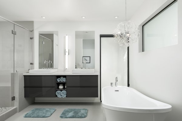 Modern home with bath room, freestanding tub, ceiling lighting, porcelain tile floor, vessel sink, engineered quartz counter, enclosed shower, wall lighting, porcelain tile wall, and two piece toilet. Master bathroom Photo 2 of Schreiber House