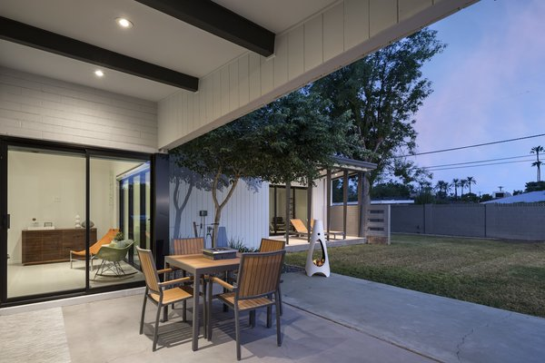 Modern home with outdoor, back yard, grass, concrete patio, porch, deck, and trees. Original patio with a view of the new addition extending beyond Photo 4 of Schreiber House