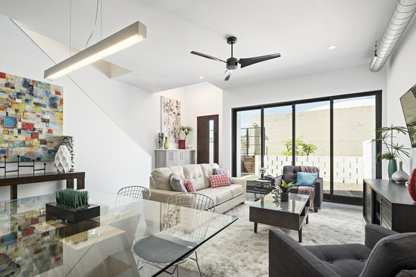 Modern home with living room, sofa, chair, concrete floor, and ceiling lighting. Sliding glass doors open up this living area to a private courtyard off of the pedestrian walkway Photo 6 of Uptown Row