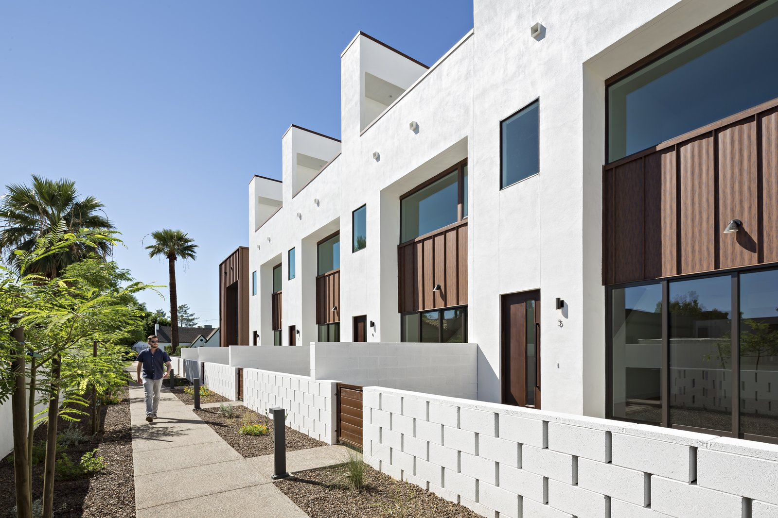Each unit in this development is accessed by a pedestrian walkway through a private courtyard. The low, spaced concrete block wall provides a social component to the development Tagged: Outdoor, Front Yard, Trees, Desert, Shrubs, Flowers, Hardscapes, Horizontal Fences, Wall, Concrete Patio, Porch, Deck, and Decomposed Granite Patio, Porch, Deck.  Uptown Row by The Ranch Mine