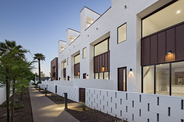 Each unit in this development is accessed by a pedestrian walkway through a private courtyard. The low, spaced concrete block wall provides a social component to the development #infill #development #townhouse #phoenix #modern #urban #wall Photo 2 of Uptown Row modern home